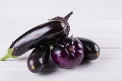 Purple eggplants of different color and variety. On the white background Royalty Free Stock Photos