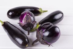Purple eggplants of different color and variety on the white background. Top view Stock Photos