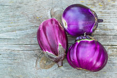 Purple eggplants on a old wooden table Royalty Free Stock Photos
