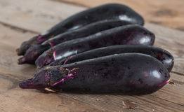 Purple eggplants on wooden background. Stock Photos
