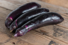 Purple eggplants on wooden background. Royalty Free Stock Photos