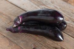 Purple eggplants on wooden background. Royalty Free Stock Photo