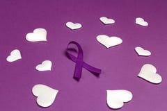 Purple epilepsy awareness ribbon wit white heats on a purple background. World epilepsy day. Purple Day royalty free stock photography