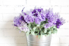 Purple fabric lavender flowers in bucket on white brick wall Stock Photos