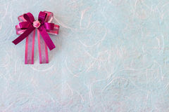 Purple fabric ribbon on blue mulberry paper. Background Royalty Free Stock Image