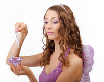 Purple fairy. Woman in a fairy costume with a magic wand an a purple diamond Royalty Free Stock Photography