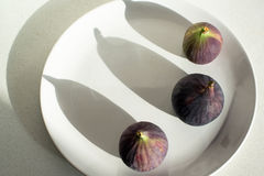 Purple figs on a white plate Stock Photos