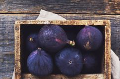 Purple figs in wooden crate on rustic wooden background Royalty Free Stock Photo
