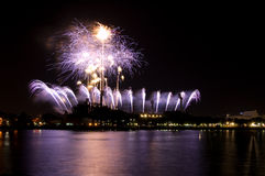 Purple Fireworks by River. A spectacular display of purple fireworks in the night sky. With beautiful reflections on the water stock photography