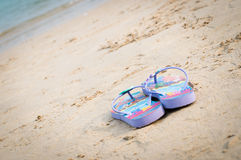 Purple flipflop. On sand beach royalty free stock image