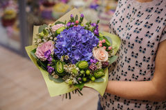 Purple flower bouquet composition in hands Royalty Free Stock Image