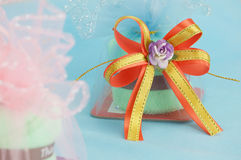 Purple flower with gold and orange ribbon bow Stock Images