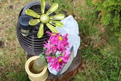 Purple flower next to yard trinkets. Bottle of flowers stock photography