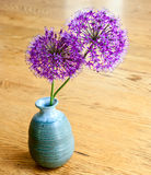 Purple flowers in a blue clay vase. Against a wood table stock illustration