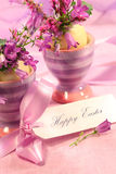 Purple flowers in eggs cups Stock Image