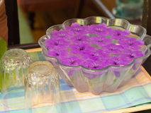 Purple flowers floating on glass jar. royalty free stock photo