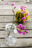 Purple flowers in glass bottles. Lilac flower in a glass bottle on a  old background Stock Photography