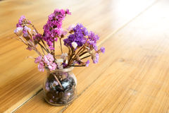 Purple flowers in a glass vase on wood table Royalty Free Stock Image