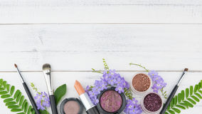 Purple flowers, green leaves, cosmetics. And make up brushes on white wood background with copy space stock image