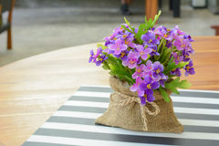 Purple flowers in small jute bag on the table Royalty Free Stock Image