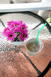 Purple flowers on table near the glass of ice. Royalty Free Stock Photos