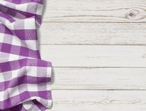 Table with purple picnic cloth top view background. Purple folded tablecloth with white wooden table Royalty Free Stock Image
