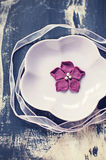 Purple fondant flower on pink plate. With pink ribbon on black wodden board Stock Photo