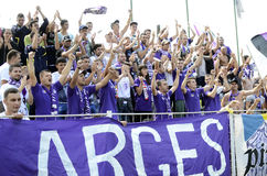 Purple Football Fans. Football fans of FC Arges cheer for their team during the first official game of the reinvented FC Arges, one of the most important Stock Photos