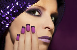 Purple French manicure. Purple French manicure and makeup on the girl with the different purple violet hues royalty free stock photography
