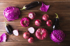Purple fruits and vegetables. Blue onion, purple cabbage, eggplant, grapes and plums. On a wooden background Stock Image