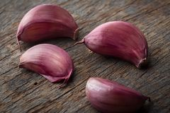 Purple Garlic Cloves. On rustic wooden table Stock Photo