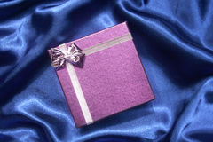 Purple gift box on blue silk. Purple gift box with silver ribbon on blue silk stock image