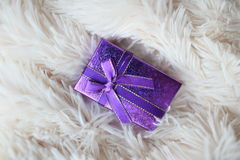 Purple gift box on a light fur rug Royalty Free Stock Photography