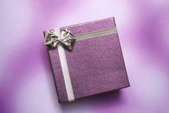 Purple gift box on purple background. Purple gift box with silver ribbon on purple background Stock Photos