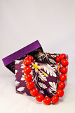 Purple gift box with red beads Stock Photos