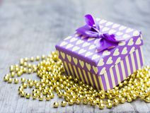 Purple gift box with yellow hearts upon golden pearls Stock Photo