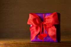 Purple gift red bow hearts Stock Image