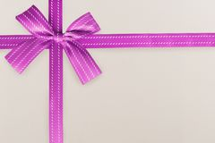 Purple gift ribbon on a white textured pattern in background. stock image