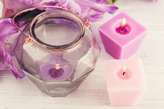Purple gladiolus and lit candles on white table. Geometrical lantern Stock Photography