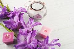 Purple gladiolus and lit candles on white table. Geometrical lantern Stock Image