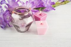 Purple gladiolus and lit candles on white table. Geometrical lantern Stock Images
