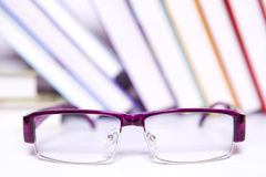 Purple glasses and  books. Purple glasses on the background of books Royalty Free Stock Images