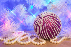 Purple glitter striped Christmas bauble with natural pearl garland Royalty Free Stock Photo
