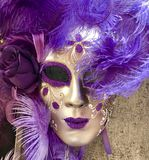 Purple and gold venetian masquerade mask hanging on a wall. A purple and gold masquerade mask hanging on a wall in Venice Italy. The mask comprises glitter Stock Photography