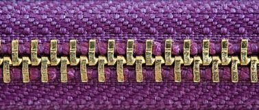 Purple and gold zipper tightly closed binding together two layers of fabric textile under high magnification close detail. Photography as texture background royalty free stock image