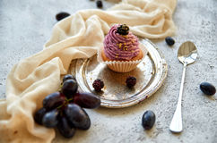 Purple golden cupcake with blackberry on silver vintage tray decorated with long spoon, light brown cloth, fresh blue grapes Royalty Free Stock Photo