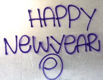 Happy new year. Purple grafitti sprayed on a white wall. A bright flare is in the top left hand corner Royalty Free Stock Photos