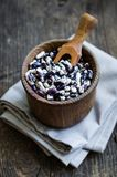 Purple grains-beens in a bowl. Dry organic purple grains-beens in a bowl on rustic wooden table. Haricot bean vegan protein source. Healthy food Stock Photo