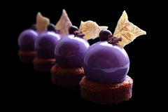 Purple grape dessert with shiny mirror glaze and chocolate decorations. Isolated on black background stock photo
