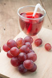 Purple grape juice in glass on a wood cutting boards. Royalty Free Stock Image